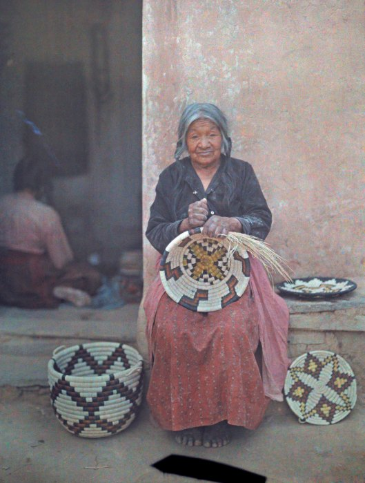 1916: Femme Hopi tenant dans ses mains le panier qu'elle vient de tresser.