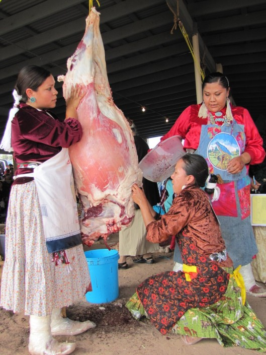 """Miss Navajo contestants must work in teams to butcher sheep. From left, Wallitta Begay, Leandra """"Abby"""" Thomas andCharlene Goodluck had to cut the sheep's throat, remove the stomach and quarter the carcass"""