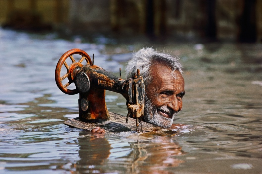 A tailor transports his sewing machine during a monsoon in Porbandar, India, in 1983