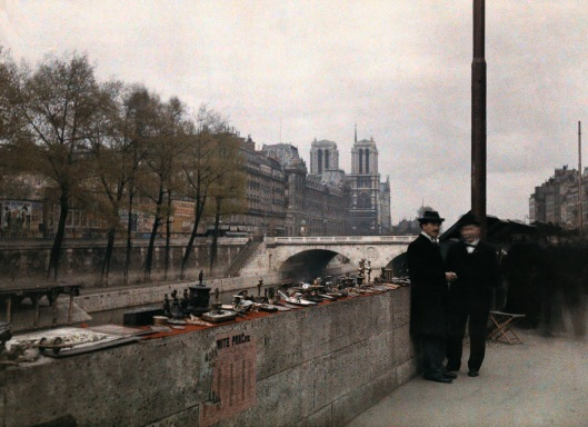 ca. January 1923, Paris, France --- Two men stand beside crafts on a street alongside a river --- Image by © Gervais Courtellemont/National Geographic Creative/Corbis
