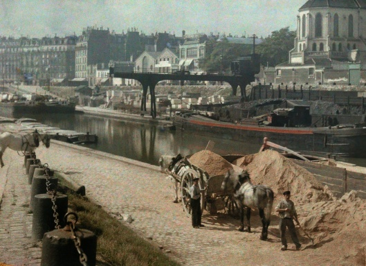 ca. January 1923, Paris, France --- Workers with horses alongside a river --- Image by © Gervais Courtellemont/National Geographic Creative/Corbis