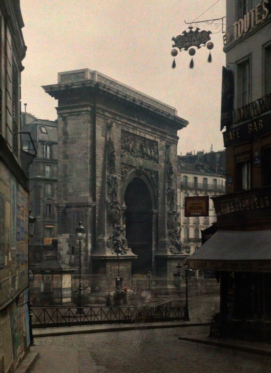 ca. January 1923, Paris, France --- A street view of the Porte Saint Denis --- Image by © Gervais Courtellemont/National Geographic Creative/Corbis