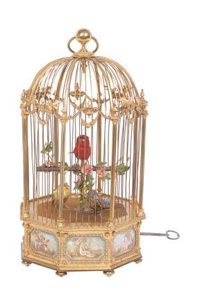 Rare cage en bronze doré à trois oiseaux chanteurs, à 8 pans coupés, ornés de plaques de porcelaine à décor polychromes de scènes du XVIIIè dans l'esprit de Sèvres. Source