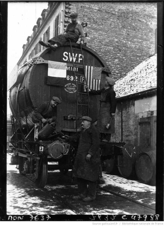 A Bercy, Halle aux vins : les marchands de vin sur un wagon-foudre ou dans un chai, fêtent l'abolition de la prohibition aux Etats-Unis. Photographie de Jacquet , 1933. Source