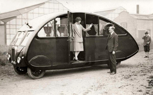 A woman standing in the doorway of an RV-camper at an exhibition in London, 1927