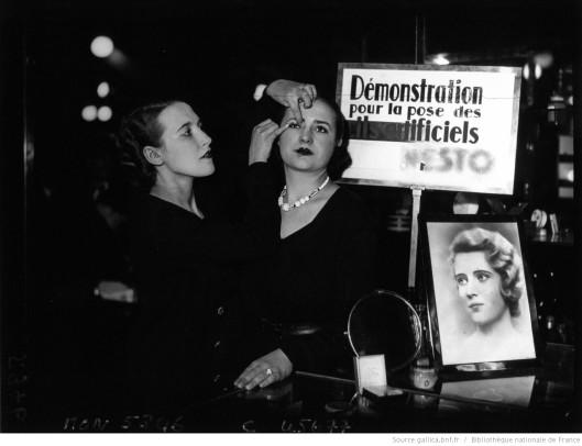 Une cliente de faux cils au rayon d'un magasin parisien , 1932. Source