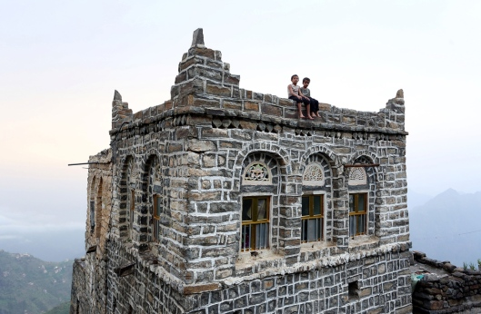 "Boys sit on an edge of the roof of their house in the mountains, in the Jafariya district of the western province of Raymah, Yemen May 31, 2016. REUTERS/Abduljabbar Zeyad SEARCH ""MOUNTAINTOP"" FOR THIS STORY. SEARCH ""WIDER IMAGE"" FOR ALL STORIES.  - RTSNCXH"