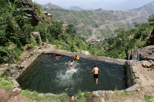 "Boys swim in a pond in the mountains, in the Jafariya district of the western province of Raymah, Yemen June 2, 2016. REUTERS/Abduljabbar Zeyad SEARCH ""MOUNTAINTOP"" FOR THIS STORY. SEARCH ""WIDER IMAGE"" FOR ALL STORIES. TPX IMAGES OF THE DAY  - RTSNCXL"