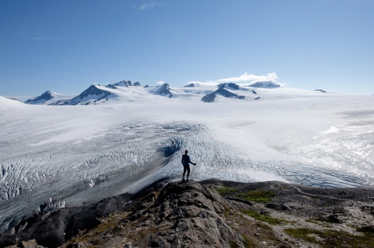 "Jessica Taft pauses above the Harding Icefield, August 27, 2016. The ice field is thousands of feet thick, but it does not completely cover the mountains; those peaks that stick through are called ""nunataks,"" from the Inuit word for ""lonely peak."""